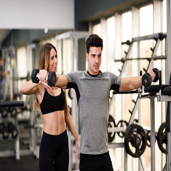 Personal trainer helping a young man lift weights