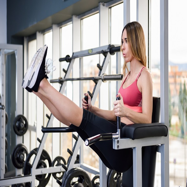 Young fit woman at the gym doing abs workout