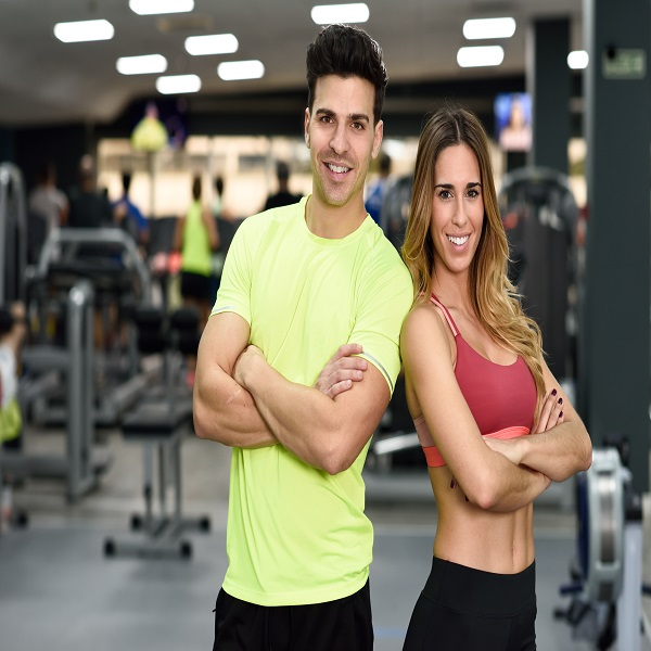 Man and woman personal trainers in the gym.
